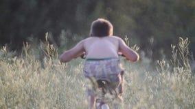 Barnet vilar på i en by med en cykel i ett högt gräs lager videofilmer