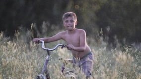 Barnet vilar på i en by med en cykel i ett högt gräs stock video