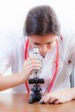 Barnet vårdar och mikroskopet Arkivfoto