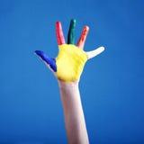 Barnets hand som målas med det mångfärgade fingret, målar på blått arkivfoton