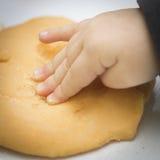 Barnets hand trycker på playdough Royaltyfri Bild