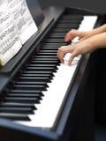 Barnets händer play pianot Arkivbild
