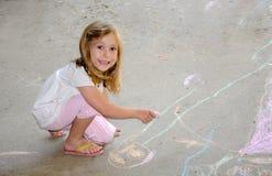 Barnfärgläggning med trottoarkrita Arkivbild