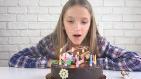 Barnfödelsedagparti som blåser stearinljus, barn årsdag, ungeberöm arkivfoton