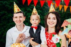 Barnfödelsedagtema familj av tre Caucasian personer som sitter i trädgården av huset på en festlig dekorerad tabell i roligt H royaltyfri bild
