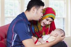 Barnföräldrar med nyfött behandla som ett barn på soffan Fotografering för Bildbyråer