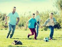 Barnföräldrar med två ungar som spelar fotboll Arkivfoton