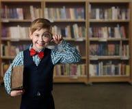 Barnförstoringsglaset, unge ser igenom förstoringsapparatloupen, boken Li arkivbild