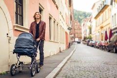 Barnfader With Baby Stroller i staden Royaltyfri Bild