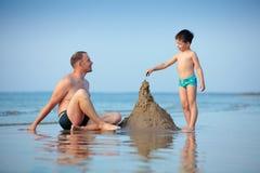 Barnfader och hans sonbyggnadssandslott Arkivfoto