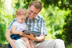 Barnfader och liten dotterläsning Fotografering för Bildbyråer