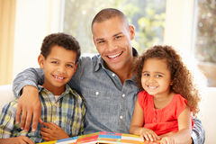 barnfader som läser till Royaltyfri Bild