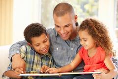 barnfader som läser till Arkivbild
