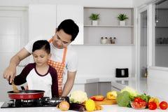 Barnfadern undervisar hans son att laga mat Royaltyfri Bild