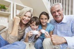 barnfamiljen spelar videopp morföräldrar Arkivbild