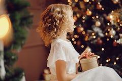 Barnflicka i ask för gåva för nytt år för jul för jultomtenhatt öppnande royaltyfri fotografi