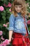 Barnflicka i den röda klänningen som spelar med rosor i sommarträdgård arkivbilder