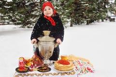 Barnflicka i ett pälslag och i en halsduk i rysk stil som rymmer en stor samovar i händerna av pannkakor med rött royaltyfria bilder