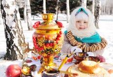 Barnflicka i ett pälslag och i en halsduk i rysk stil som rymmer en stor samovar i händerna av pannkakor med rött royaltyfri bild