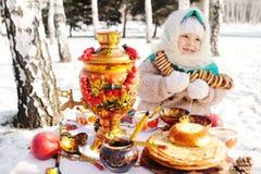 Barnflicka i ett pälslag och i en halsduk i rysk stil som rymmer en stor samovar i händerna av pannkakor med rött arkivfoto