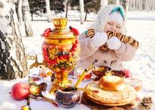 Barnflicka i ett pälslag och i en halsduk i rysk stil som rymmer en stor samovar i händerna av pannkakor med rött arkivbilder