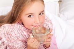 Barnflicka med en kopp av varmt te i säng arkivfoto