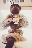 Barnflicka med en vit kopp av den varma drinken Arkivfoto