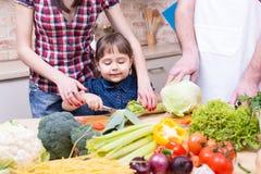 Barnflicka med modern och fadern som tillsammans lagar mat Royaltyfri Foto