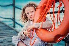 Barnflicka med räddningsaktioncirkeln på träpir med havsbakgrund royaltyfria bilder