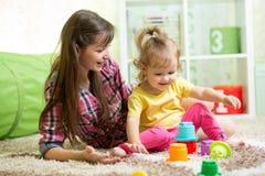 Barnflicka och hennes moder som spelar samman med leksaker Royaltyfri Bild