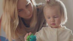 Barnflicka och hennes moder som spelar samman med leksaker stock video