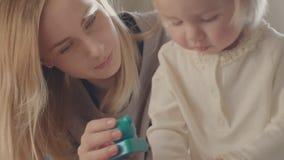 Barnflicka och hennes moder som spelar samman med leksaker lager videofilmer