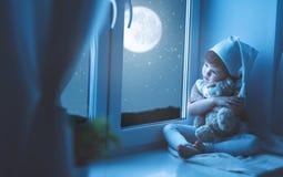 Barnflicka på fönstret som drömmer stjärnklar himmel på läggdags royaltyfri foto