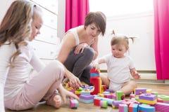 Barnflicka samman med modern och systern som spelar bildande leksaker arkivfoton