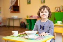 Barnflicka som är klar att äta mat på dagiset arkivfoton