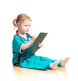 Barnflicka som är uniformerad som doktorn som skriver till skrivplattan som isoleras på Arkivbilder