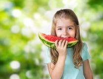 Barnflicka som äter skivavattenmelon på grön suddighetsbakgrund royaltyfri bild