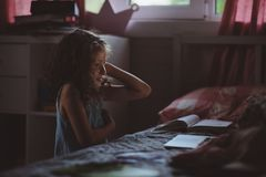 Barnflicka som använder bärbara datorn och håller ögonen på filmer på natten bara i hennes rum Arkivfoton