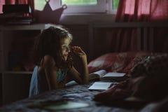Barnflicka som använder bärbara datorn och håller ögonen på filmer på natten bara i hennes rum Royaltyfri Bild