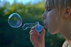 Barnflicka som blåser såpbubblor Arkivfoto