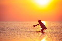 Barnflicka som går på solnedgånghavet arkivbild