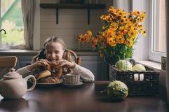 Barnflicka som har frukosten hemma i höstmorgon Hemtrevlig modern inre för verkliga livet i landshus Fotografering för Bildbyråer