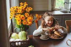 Barnflicka som har frukosten hemma i höstmorgon Hemtrevlig modern inre för verkliga livet i landshus Arkivbild