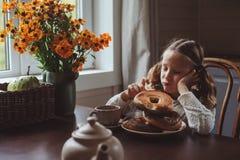 Barnflicka som har frukosten hemma i höstmorgon Hemtrevlig modern inre för verkliga livet i landshus Arkivbilder