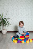 Barnflicka som har gyckel och byggande av ljusa plast- konstruktionskvarter Litet barn som spelar på golvet Framkallande leksaker Arkivfoton