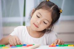barnflicka som har gyckel som spelar och som lär magnetiska alfabet royaltyfri fotografi