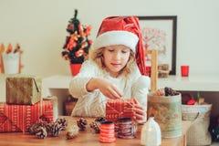 Barnflicka som hemma förbereder gåvor för jul, hemtrevlig ferieinre Royaltyfri Fotografi