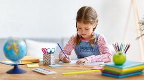 Barnflicka som hemma gör läxahandstil och läsning arkivbilder
