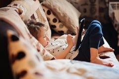 Barnflicka som hemma spelar minnestavlan Arkivfoto