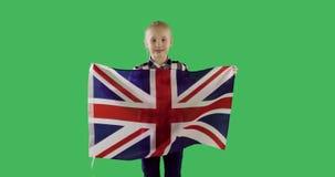 Barnflicka som rymmer den engelska flaggan på den nyckel- gröna skärmen för chroma lager videofilmer